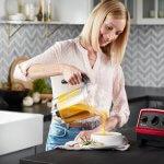 nainen kaataa kuumaa kurpitsakeittoa lautaselle vitamixkannusta